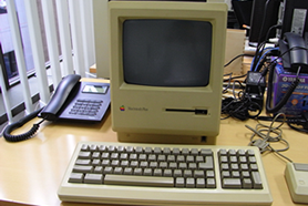 Macintosh Plusとキーボードが電話などと一緒にオフィスの机に置いてある様子。