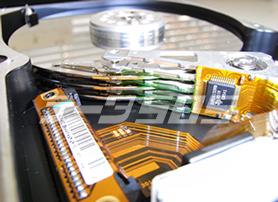 ハードディスクを開封した様子。3枚のプラッターそれぞれの裏表に磁気ヘッドのアームが延びている。